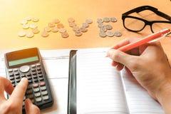 Человеческие примечание сочинительства ручки удерживания руки и калькулятор подсчитывать на d Стоковое Изображение RF
