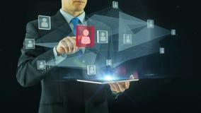 Человеческие ресурсы чернят бизнесмена концепции управления выбирая виртуальный интерфейс указывая на стеклянный hologram значков акции видеоматериалы