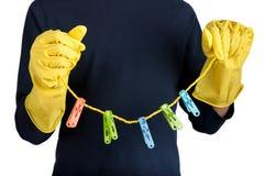 Человеческие руки в перчатках держат веревку для белья и зажимки для белья Стоковое Изображение