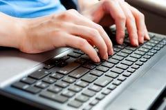 Человеческие руки на конце клавиатуры компьтер-книжки вверх стоковое фото rf