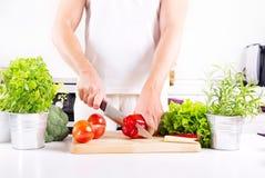 Человеческие руки подготавливая овощи в кухне Стоковое Изображение