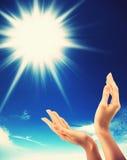 Человеческие руки, солнце и голубое небо Стоковое Фото