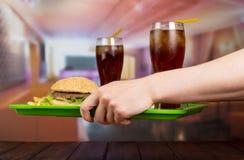 Человеческие руки с подносом вкусного гамбургера Стоковая Фотография