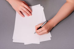 Человеческие руки с сочинительством карандаша на бумаге и резине стирания на предпосылке деревянного стола Стоковое Изображение