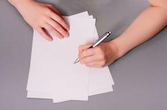 Человеческие руки с сочинительством карандаша на бумаге и резине стирания на предпосылке деревянного стола Стоковые Фото