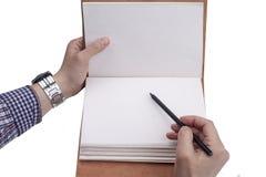 Человеческие руки с сочинительством карандаша на бумаге на белой предпосылке Стоковые Изображения RF