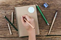 Человеческие руки с сочинительством карандаша на бумаге на деревянном столе Стоковые Изображения