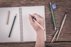 Человеческие руки с сочинительством карандаша на бумаге на деревянном столе Стоковое фото RF