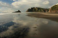 Человеческие следы ноги на пляже Karekare стоковые фото