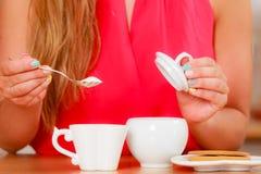 Человеческий добавляя сахар к чаю или кофе стоковые фотографии rf