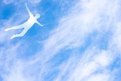 Человеческий силуэт в полете против неба Стоковое фото RF
