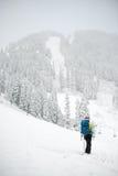 Человеческий фронт стойки гор на снеге в зиме Стоковое Изображение