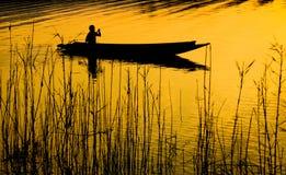Человеческий rowing на шлюпке над драматическим заходом солнца стоковое фото