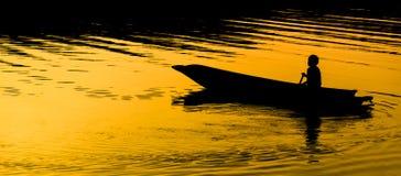 Человеческий rowing на шлюпке над драматическим заходом солнца Стоковое фото RF