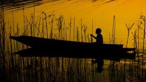 Человеческий rowing силуэта на шлюпке над драматическим заходом солнца, человеческим Стоковые Изображения RF
