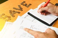 Человеческое примечание на столе, сбережения сочинительства ручки удерживания руки, финансы, e Стоковые Фотографии RF