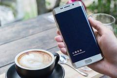ЧИАНГМАЙ, ТАИЛАНД - НОЯБРЬ 20,2015: Рука человека держа экран гостеприимсва Uber app показывая на крае галактики s6 Samsung, Uber Стоковая Фотография RF