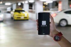 ЧИАНГМАЙ, ТАИЛАНД - 23-ЬЕ АВГУСТА 2016: Рука человека держа Uber app Стоковое Изображение RF