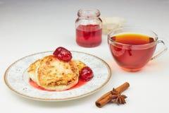 Чизкейки на поддоннике с вареньем и чаем блинчики творога или блинчики с вареньем клубники и чашкой чаю на белом стоковая фотография