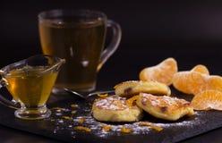 Чизкейки с изюминками, обломоками tangerine и напудренным сахаром Затем куски мандарина, меда и чашки зеленого чая стоковые изображения
