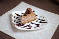 Чизкейк шоколада с соусом шоколада на белой плите Стоковые Изображения RF