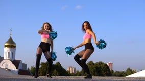 2 чирлидера девушек с помпонами танцуя outdoors акции видеоматериалы