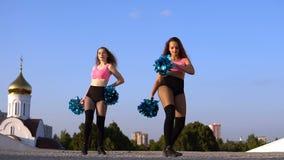 2 чирлидера девушек с помпонами танцуя outdoors видеоматериал