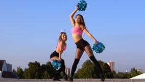 2 чирлидера девушек с помпонами танцуя outdoors сток-видео