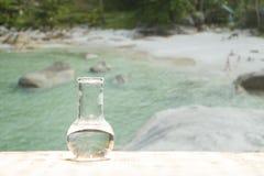Чистая вода в стеклянной склянке лаборатории на деревянном столе на предпосылке моря Экологическая концепция, защита воды Стоковое Фото