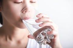Чистая вода молодой женщины выпивая в ее руке Стоковое Изображение RF