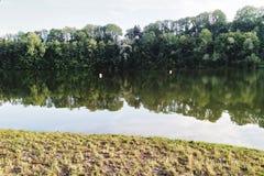 Чистая вода, отражая деревья, время поплавать стоковое фото