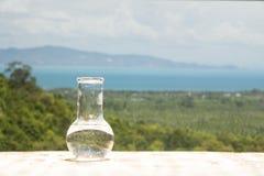 Чистая вода в стеклянной склянке лаборатории на деревянном столе на предпосылке моря Экологическая концепция, защита воды Стоковая Фотография