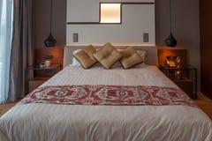 Чистая спальня гостиницы с светом кровати открытым Стоковые Изображения RF