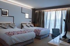 Чистая спальня гостиницы с светом кровати открытым Стоковое фото RF