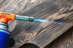 Чистить щеткой с газовой горелкой дома Обрабатывать мягкую часть древесины с огнем Украшение деревянных продуктов стоковые фото