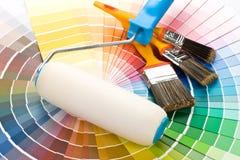 чистит ролик щеткой краски
