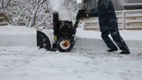 Чистка зимы Неизвестный человек в прозодеждах, снег-извлекая снегоочиститель в жилом микро- районе в зиме, много сток-видео