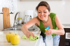 Чистка молодой женщины в кухне Стоковое Изображение RF