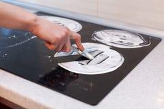 Чистка дома Чистка домохозяйки и электрическая плита заполированности Черная сияющая поверхность верхней части кухни, рук с пеной Стоковое Изображение
