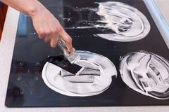 Чистка дома Чистка домохозяйки и электрическая плита заполированности Черная сияющая поверхность верхней части кухни, рук с пеной Стоковые Фотографии RF