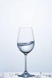 Чисто волна воды в бокале пока стоять на стекле с водой клокочет против светлой предпосылки стоковые изображения
