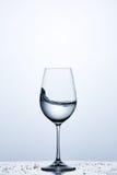 Чисто волна воды в бокале пока стоять на стекле с задрапировывает против светлой предпосылки стоковые изображения