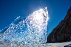 Чисто прозрачный лед Lake Baikal через солнце сияющий в заходе солнца стоковые изображения