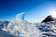 Чисто прозрачный лед Lake Baikal через солнце сияющий в заходе солнца стоковые фото