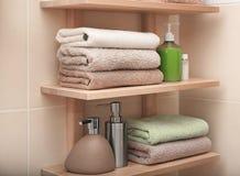 Чистые полотенца и косметики на полках Стоковая Фотография