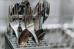 Чистые сухие вилки и ложки в открытом крупном плане судомойки конец-вверх отсека столового прибора i стоковое изображение