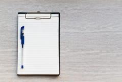 Чистый лист бумаги в доске сзажимом для бумаги и ручка на деревянном столе Стоковые Фото