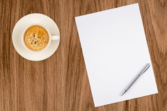 Чистый лист бумаги с ручкой и кофейная чашка на деревянной таблице Стоковая Фотография