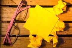 Чистый лист бумаги Ellow с скомканной бумагой с стеклами на деревянное pettern стоковые изображения rf