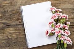 Чистый лист тетради и красной и белой гвоздики Стоковое Фото